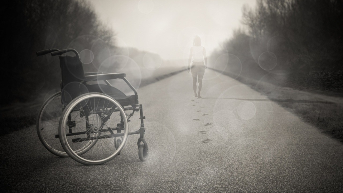 Frau steht aus Rollstuhl auf
