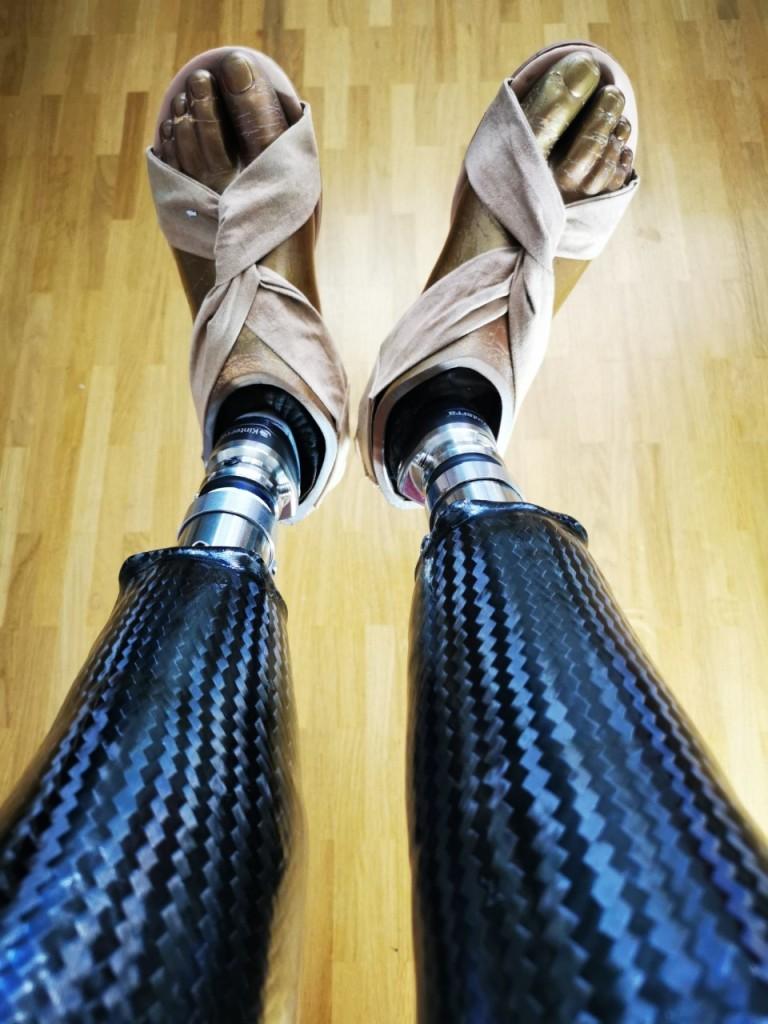 2 schwarze Beinprothesen aus Carbon mit Fußkosmetik- Perspektivenwechsel mit Prothesen