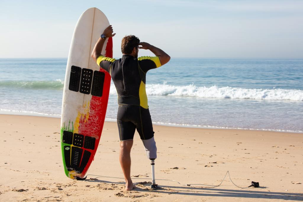 Surfer mit Board und Beinprothese steht am Meer- Perspektivenwechsel mit Prothesen